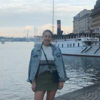Cecilia Pettersson standing and smiling outside, with water, a boat and an old building behind her