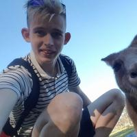 Denis squats to take a selfie with a kangaroo