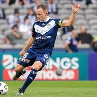 Leigh Broxham in a stadium poised to kick a soccer ball, one arm in the air