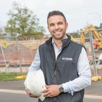 Michael Tabone in a Vic Permits vest, in front of a construction site, holding a hard hat, with two people behind him looking at paperwork