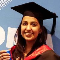 Alia Asif smiling in graduation cap and gown