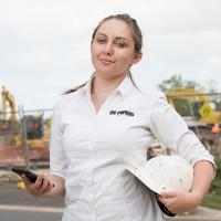 Violetta Jakielaszek in front of a construction site holding a hard hat and a mobile phone